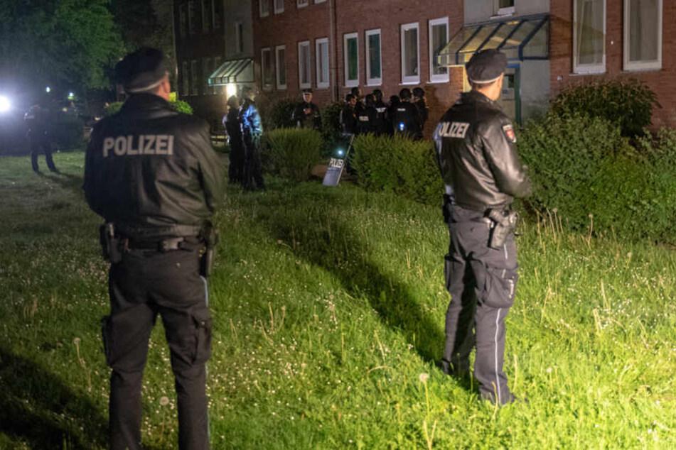 Polizeibeamte stehen vor einem Wohnhaus in Rahlstedt.
