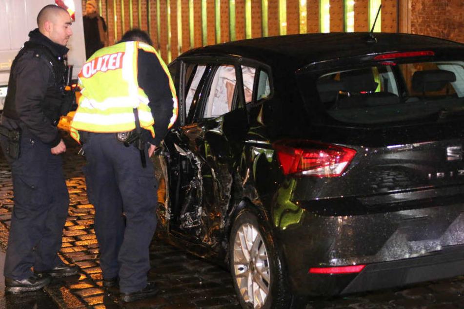 Polizisten betrachten den demolierten Wagen.