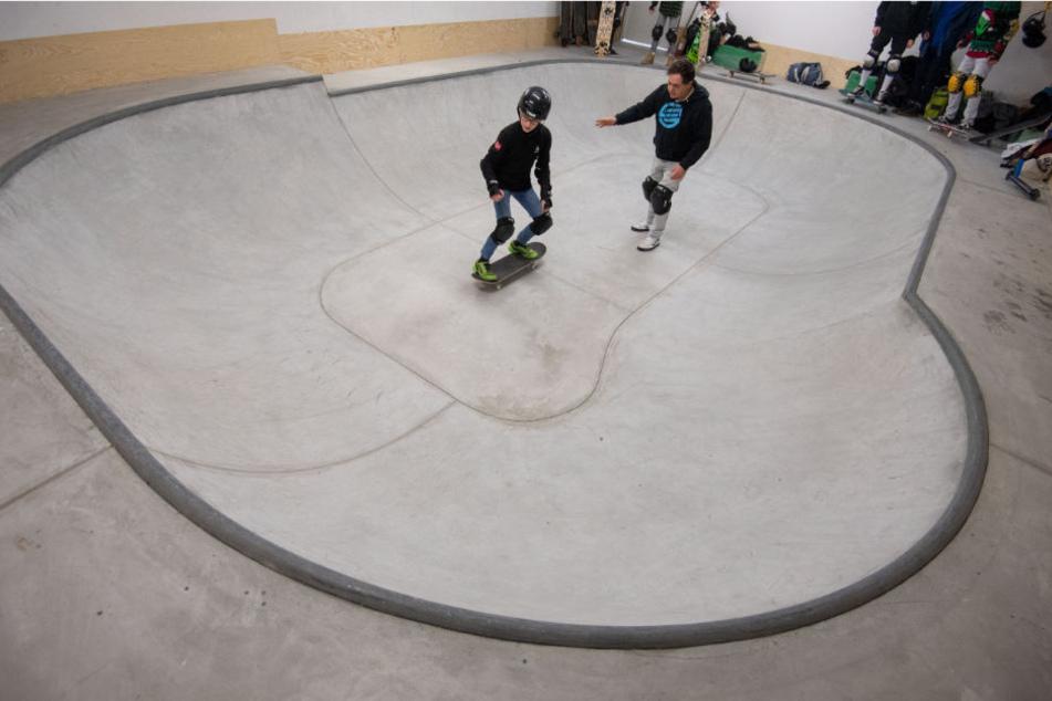 Der Lehrer leitet einen Schüler in der Skateboard-Anlage des Gymnasiums an.