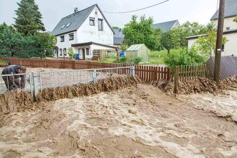 Braune Wassermassen wälzen sich nach heftigen Regenfällen am Samstag durch Gehringswalde im Erzgebirge.