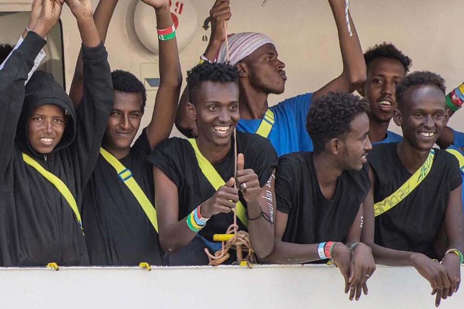 Migranten und Besatzungsmitglieder des Rettungsschiffes Aquarius winken beim Einlaufen in den Hafen von Senglea. (Symbolbild/Archivbild)