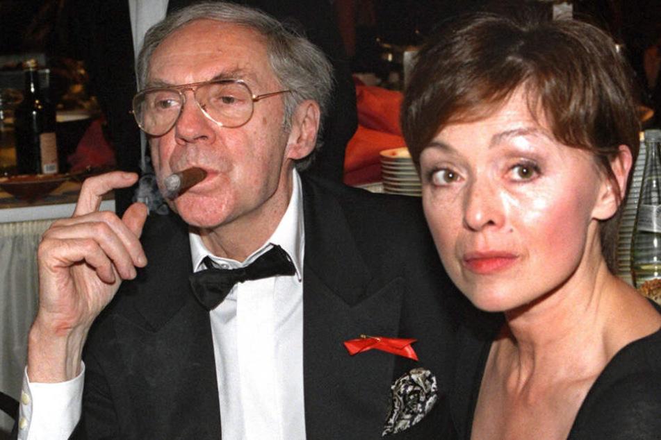 An einer Zigarre zieht Schauspieler Harald Juhnke neben seiner Frau Susanne bei einer Gala. Seine Karriere dauerte 50 Jahre.