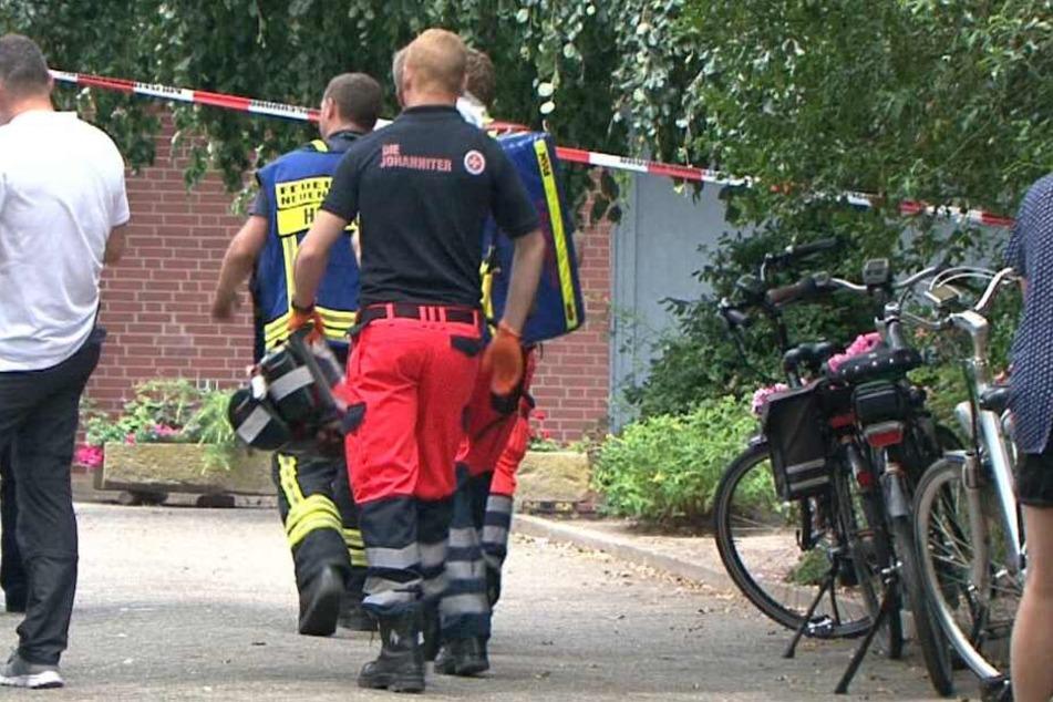 Rettungskräfte betreten das Grundstück in Neuenkirchen, auf dem die Leiche gefunden wurde.