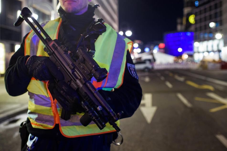 Ein bewaffneter Polizist steht an einer Zufahrt zum Weihnachtsmarkt an der Gedächtniskirche.