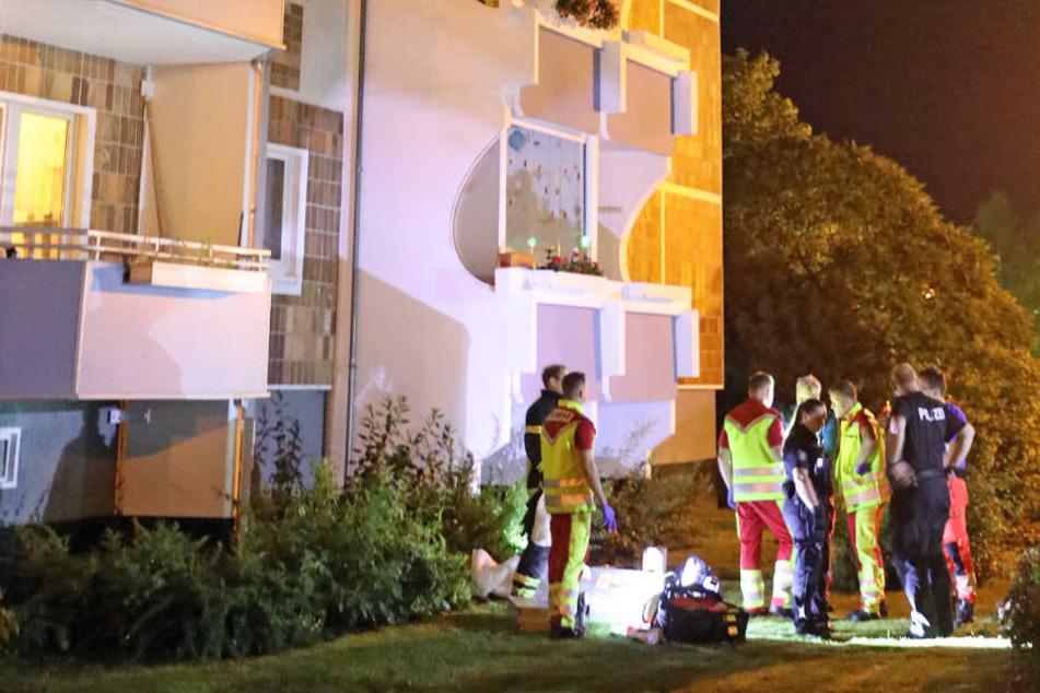 Feuerwehrleute und Polizisten stehen vor dem Hochhaus in Rostock.