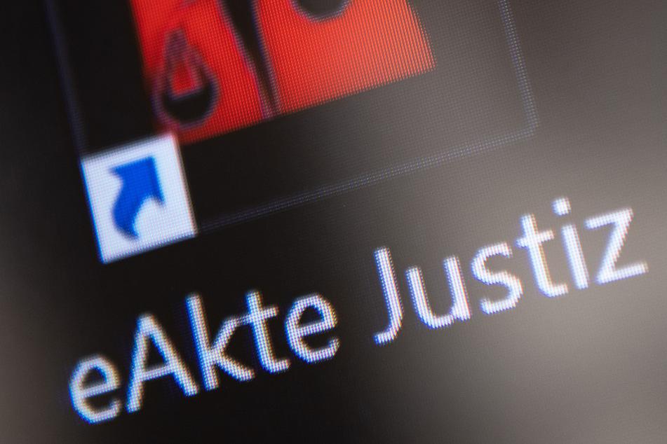 """Das Logo der """"eAkte Justiz"""" ist während einer Pressekonferenz nach der Einführung der elektronischen Akte auf einem Monitor zu sehen."""