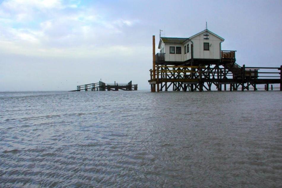 Ein Pfahlbau steht am während einer kleinen Sturmflut am Strand von Sankt Peter-Ording in Schleswig-Holstein im Wasser.