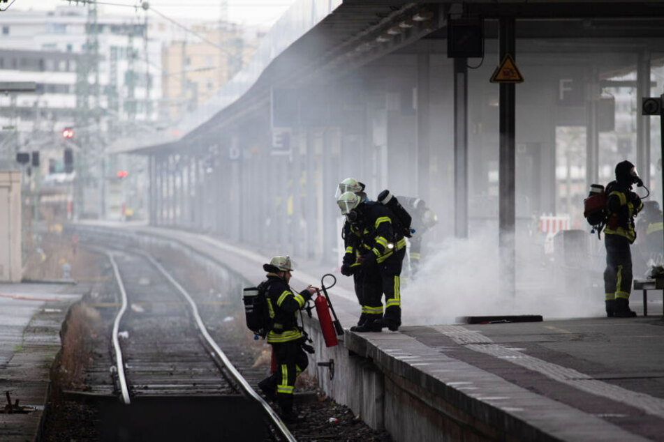Feuerwehrleute mit einem Feuerlöscher an den Gleisen.