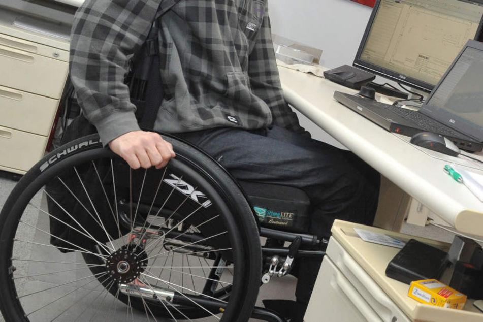 Ein Mann sitzt in einem Rollstuhl an seinem Arbeitsplatz am Schreibtisch.