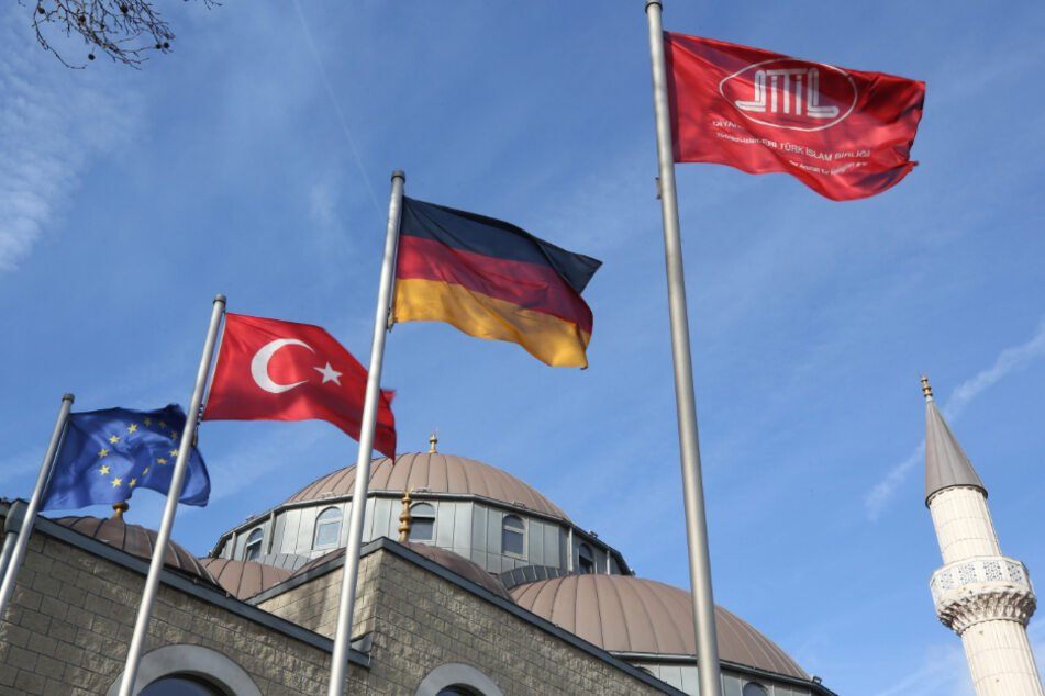 Vor der DITIB-Merkez-Moschee wehen Fahnen von Europa, der Türkei, Deutschland und die Moscheefahne. (Archiv)