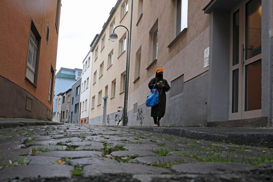 Eine Frau mit einem Tuch vor Mund und Nase geht durch eine Gasse. Nach den vorliegenden Zahlen gelten mittlerweile fast alle Regionen in NRW als Corona-Risikogebiete.