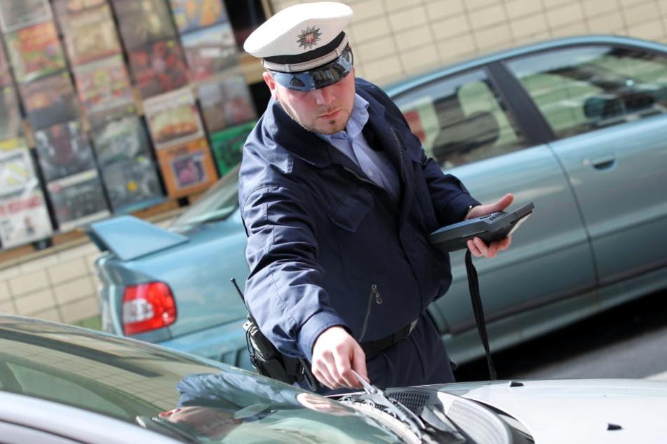 Ein Beamter verteilt einen Strafzettel an einen Falschparker. Die Verkehrssünder werden künftig auch in den späten Abend- und Nachtstunden zur Rechenschaft gezogen. (Symbolbild)
