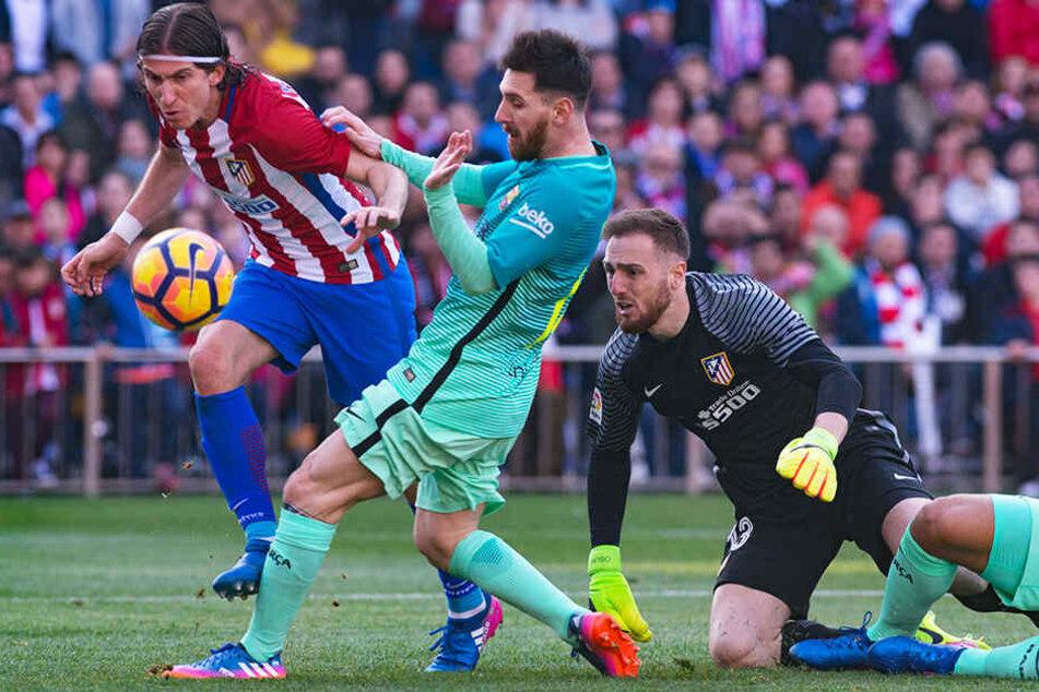 Filipe Luís (l.) knöpft hier Barcelonas Superstar Lionel Messi (M.) den Ball ab.