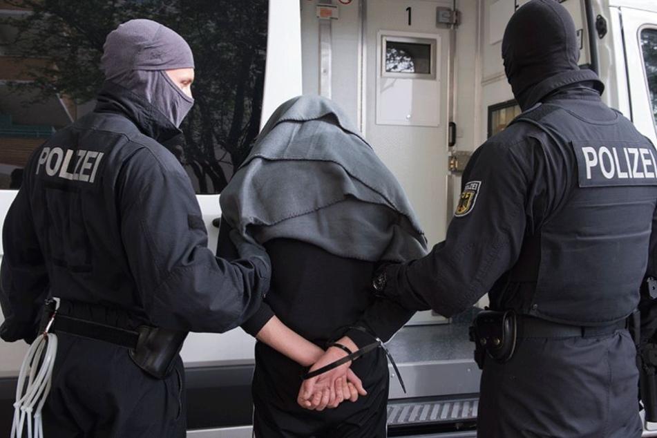 Die Polizei führt einen der Verdächtigen ab.