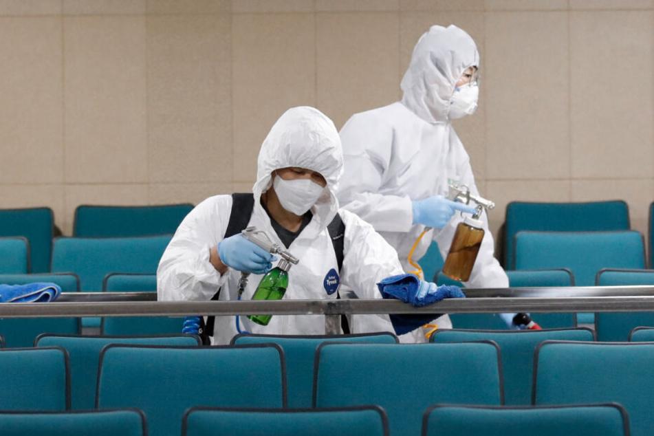 Südkorea, Seoul: Arbeiter in Schutzanzügen sprühen Desinfektionsmittel als Vorsichtsmaßnahme gegen die Ausbreitung des neuen Coronavirus in einer Sporthalle.