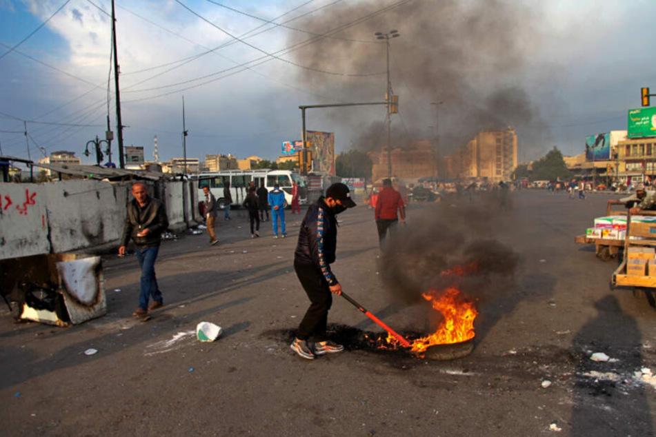 Ein Demonstrant legt während eines Protests gegen den iranischen Raketenangriffe auf US-Stützpunkte im Irak in der Nähe des Tahrir-Platzes in Bagdad ein Feuer.
