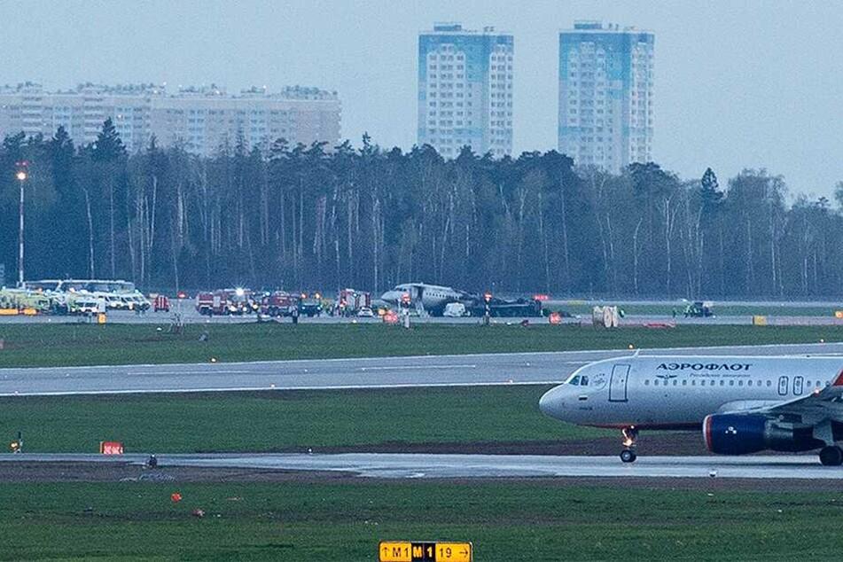 Eine Aeroflot-Maschine des Typs Suchoi Superjet-100 steht nach Löscharbeiten auf dem Rollfeld des Flughafens Scheremetjewo und ist von Einsatzkräften umgeben.