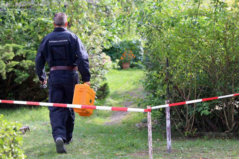 Ein Kriminaltechniker geht zum Fundort der Leichen.