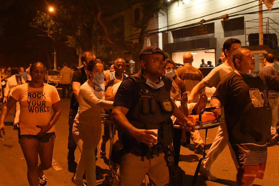 Menschen transportieren eine verletzte Person nach dem Brand im Krankenhaus Badim.