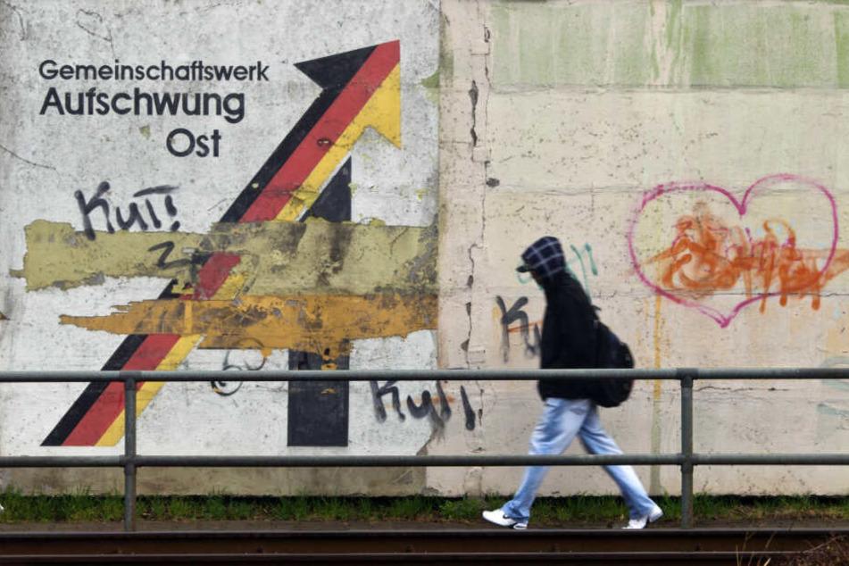 """Ein Passant geht an einer Schallschutzmauer an einem aus der Wendezeit stammenden verwitterten Wandbild mit dem Schriftzug """"Gemeinschaftswerk Aufschwung Ost"""" in Magdeburg vorbei."""