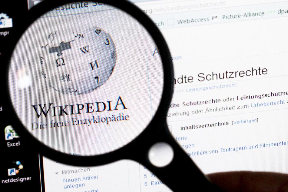 Unter einer Lupe ist das Logo der Wikipedia auf einem Bildschirm zu sehen.