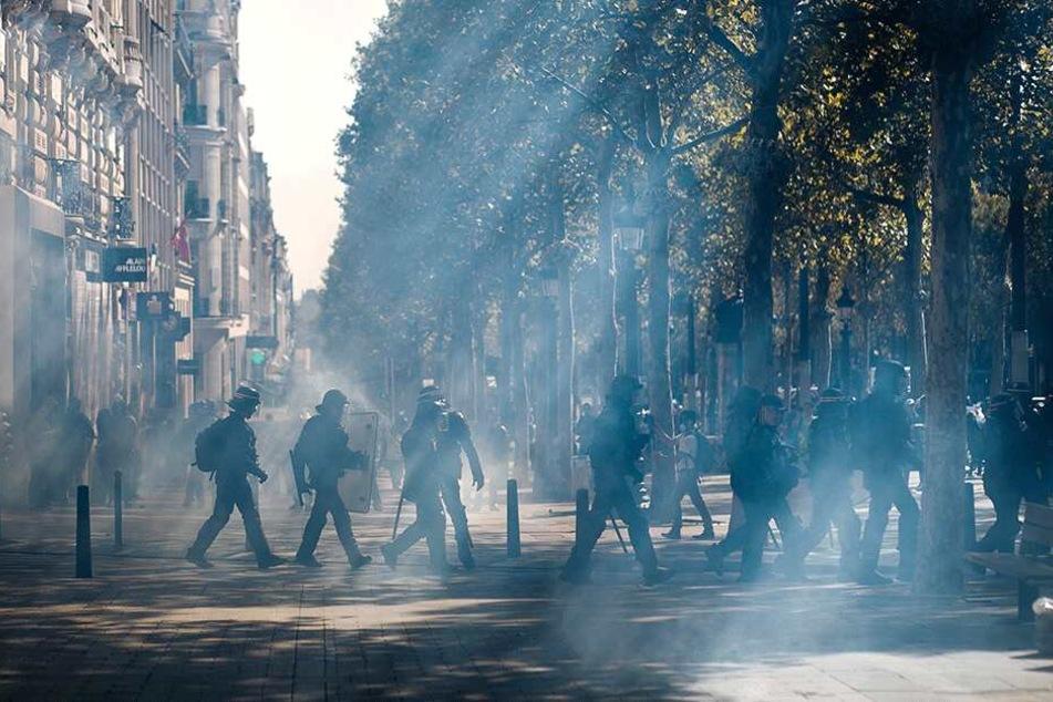 """Französische Bereitschaftspolizei geht während der """"Gelbwesten""""-Demonstration durch eine Tränengaswolke auf den Champs-Élysées."""