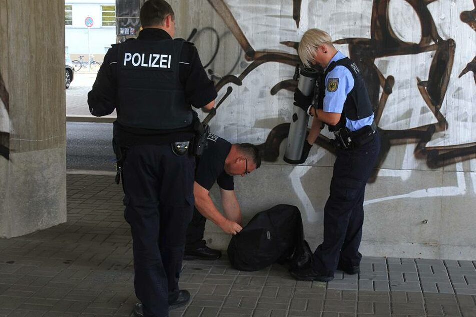 Vorsichtig inspizieren die Beamten den Koffer.