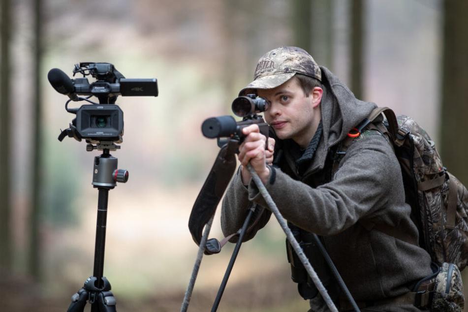 Der Jäger Rouven Kreienmeier steht mit Büchse und Filmkamera in einem Waldstück von einem Jagdrevier. Er berichtet auch per Youtube-Kanal.