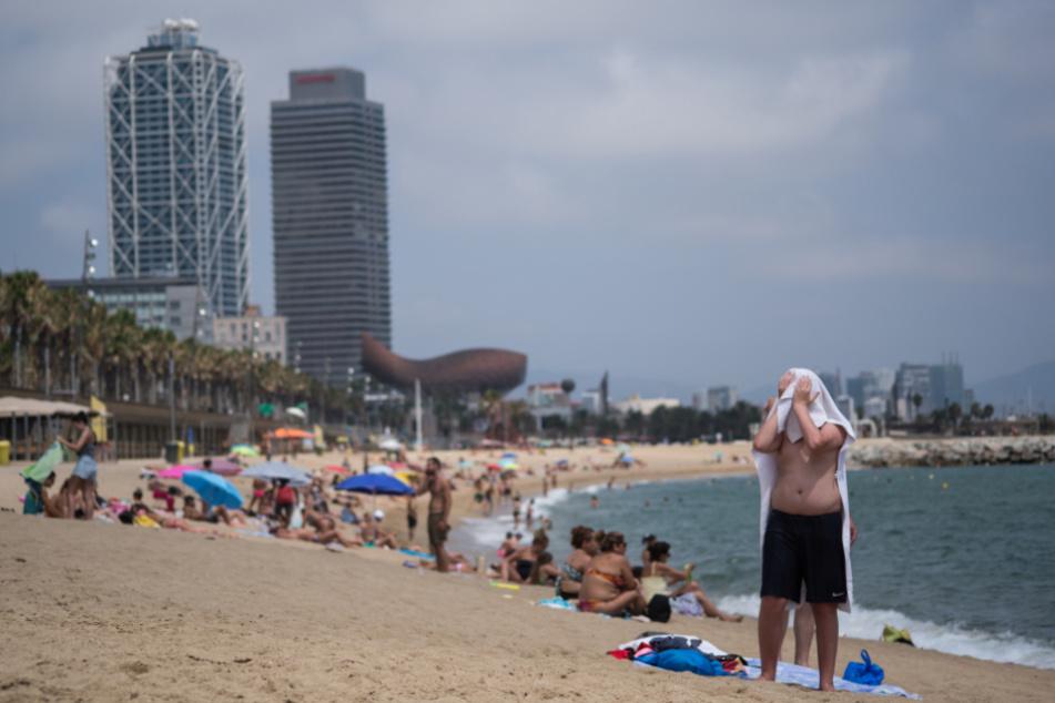 Spanien, Barcelona: Ein Mann trocknet sich mit einem Handtuch am Strand von Barceloneta ab.
