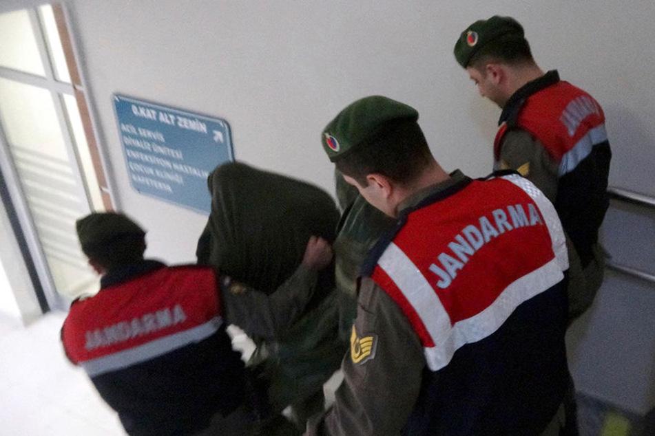 Türkische paramilitärische Polizisten führen die zwei griechischen Soldaten aus einem Gebäude heraus.