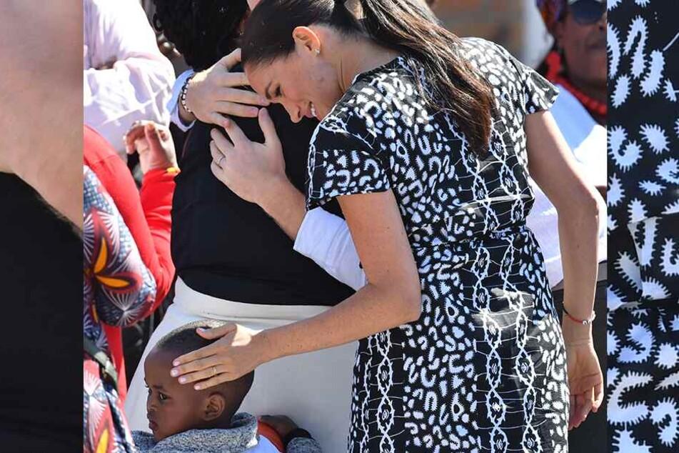 Meghan (38), Herzogin von Sussex, streicht einem Kind über den Kopf, während der britische Prinz Harry (35), dahinter eine Frau umarmt.