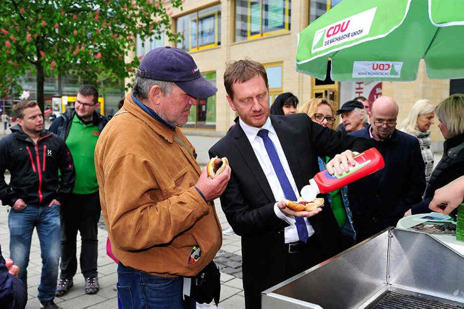 MP Michael Kretschmer (44, CDU) verteilte Donnerstag Bratwürste vor dem Roten Turm und beantwortete Fragen der Bürger.