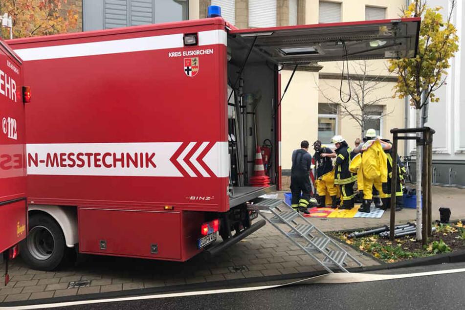 Feuerwehrleute in Schutzanzügen begannen mit Messungen auf radioaktive Strahlung in der Umgebung.