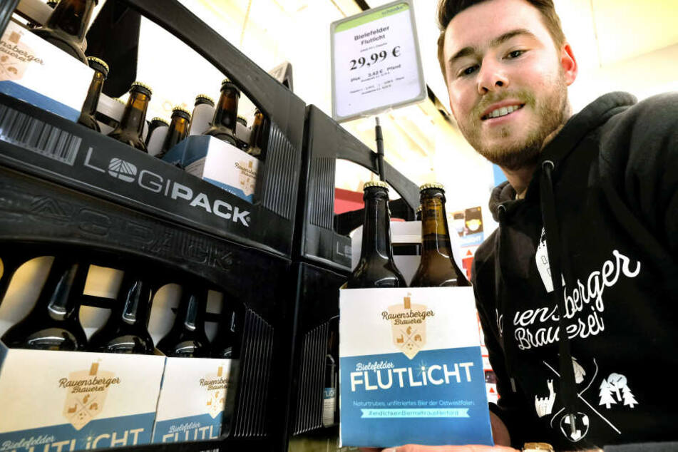 Mike Cacic hält stolz sein eigenes Bier hoch.