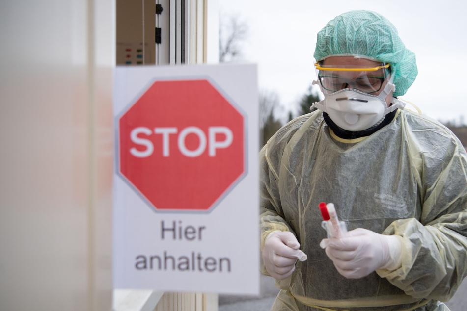 """Eine Mitarbeiterin eines Krankenhauses hat während eines Pressetermins zum Start einer """"Drive-In""""-Teststation an einem Container Teströhrchen in der Hand (Archivbild)."""