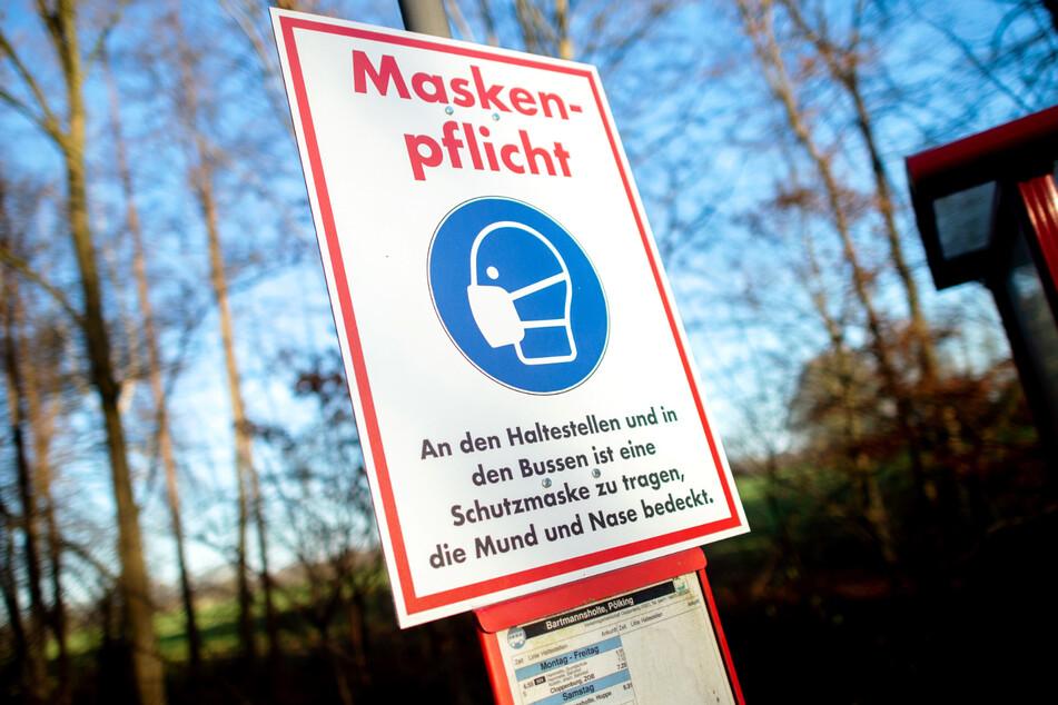 """Ein Schild mit der Aufschrift """"Maskenpflicht"""" hängt an einer Bushaltestelle."""