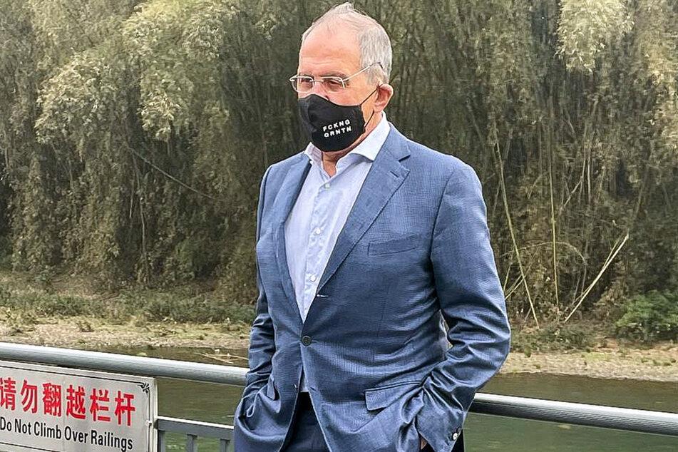"""Wer der englischen Sprache mächtig ist: Russlands Außenminister Sergej Lawrow (71) trägt bei seinem China-Besuch eine Gesichtsmaske mit der Aufschrift """"FCKNG QRNTN""""."""