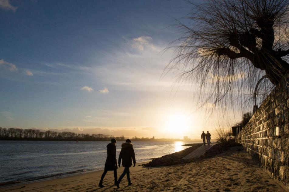 Menschen gehen am Elbstrand bei Ovelgönne im Licht des Sonnenuntergangs spazieren. So traumhaft soll es die kommenden Tage werden.