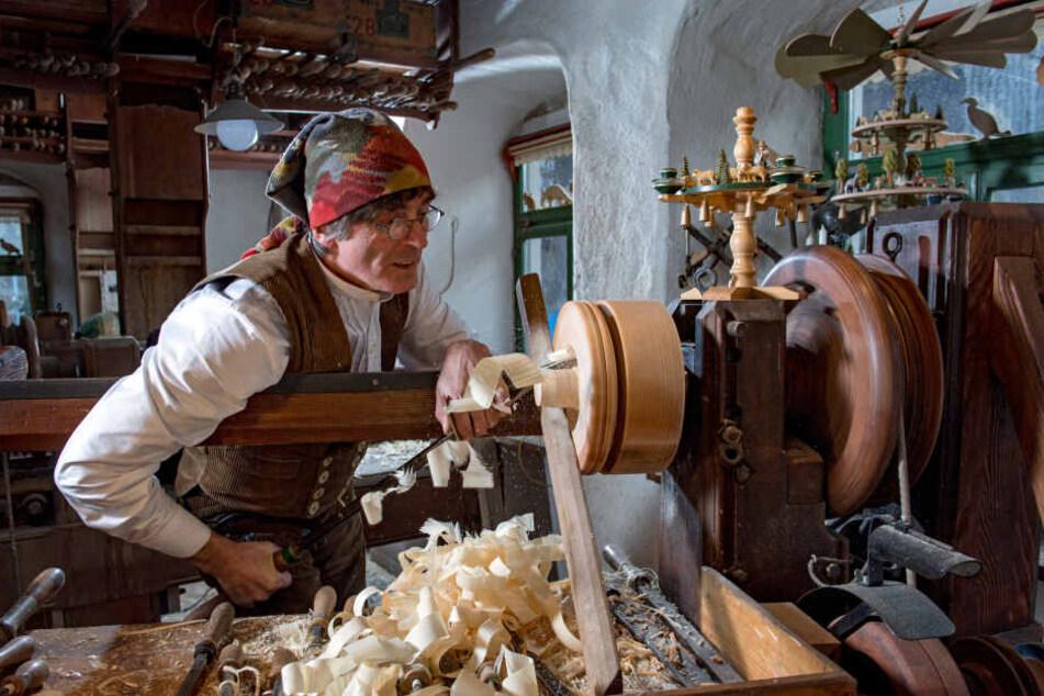 Christian Werner (61), einer der letzten Reifendreher, arbeitet in seiner Werkstatt in Seiffen an der Drehbank.