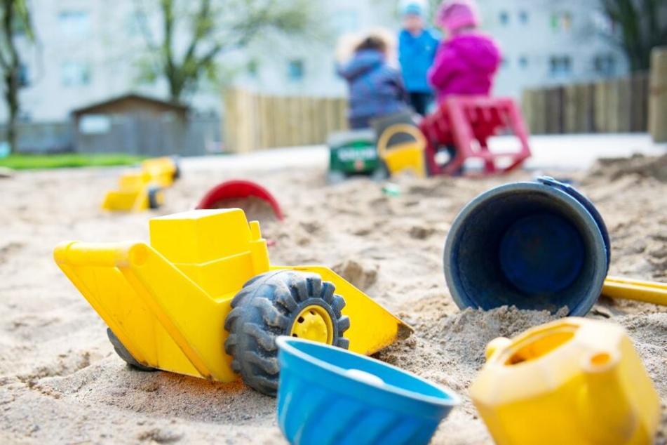 Spielzeug liegt in einem Sandkasten in einer Kindertagesstätte.