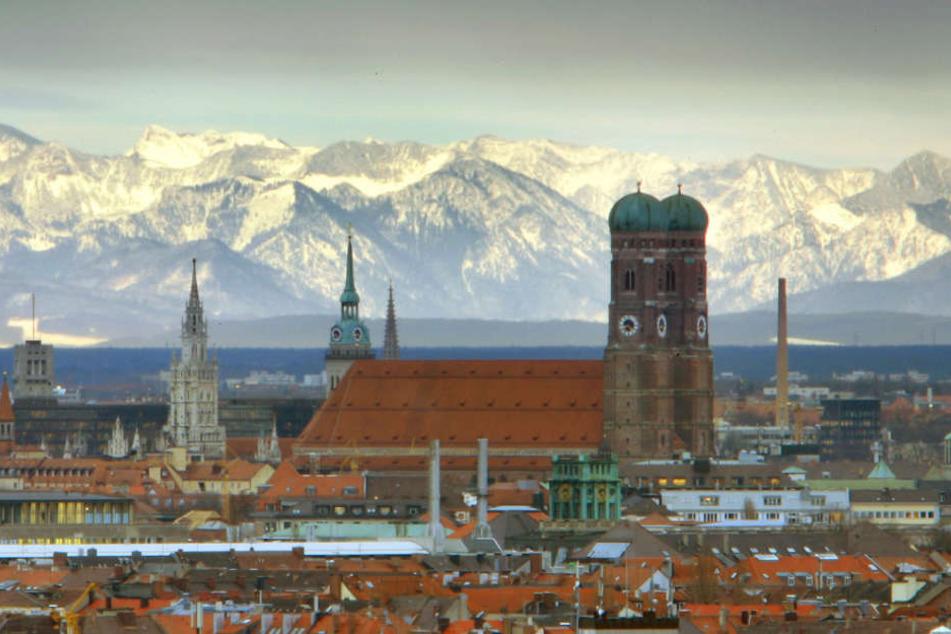 Die Münchner Frauenkirche ist vor den schneebedeckten Alpen zu sehen.
