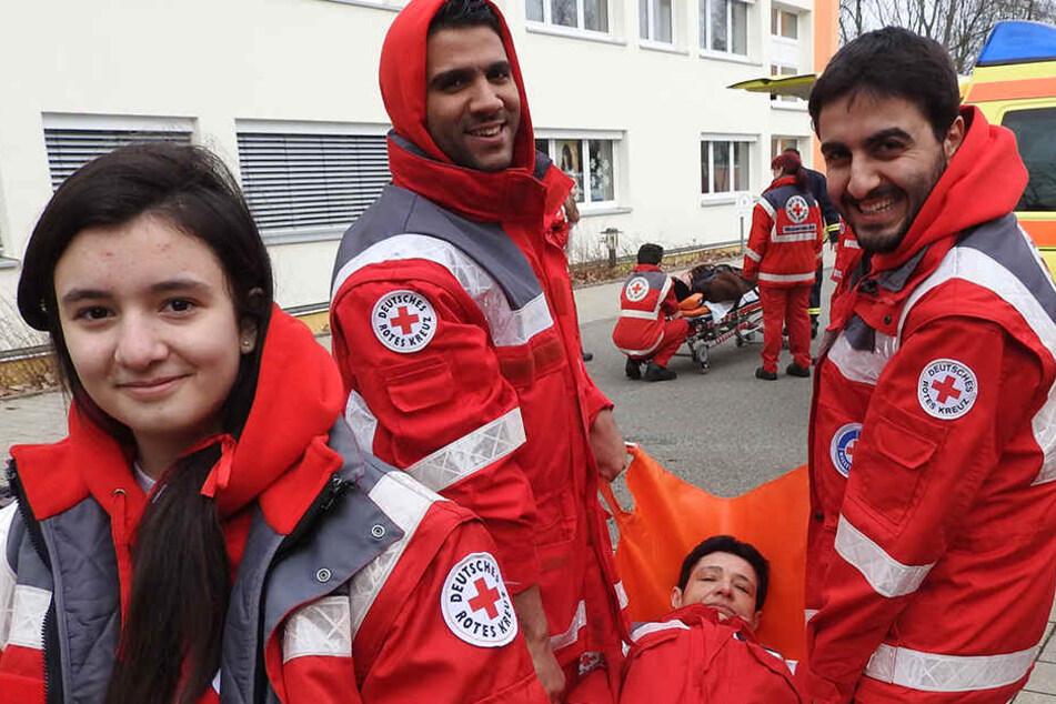 Schön, dass sie helfen: Youmna aus Syrien, Walid (Palästina, v.l.) und Omar aus Syrien (r.) tragen Wasserwacht-Kollegin Simone (im Tragetuch) mit Händen .. .