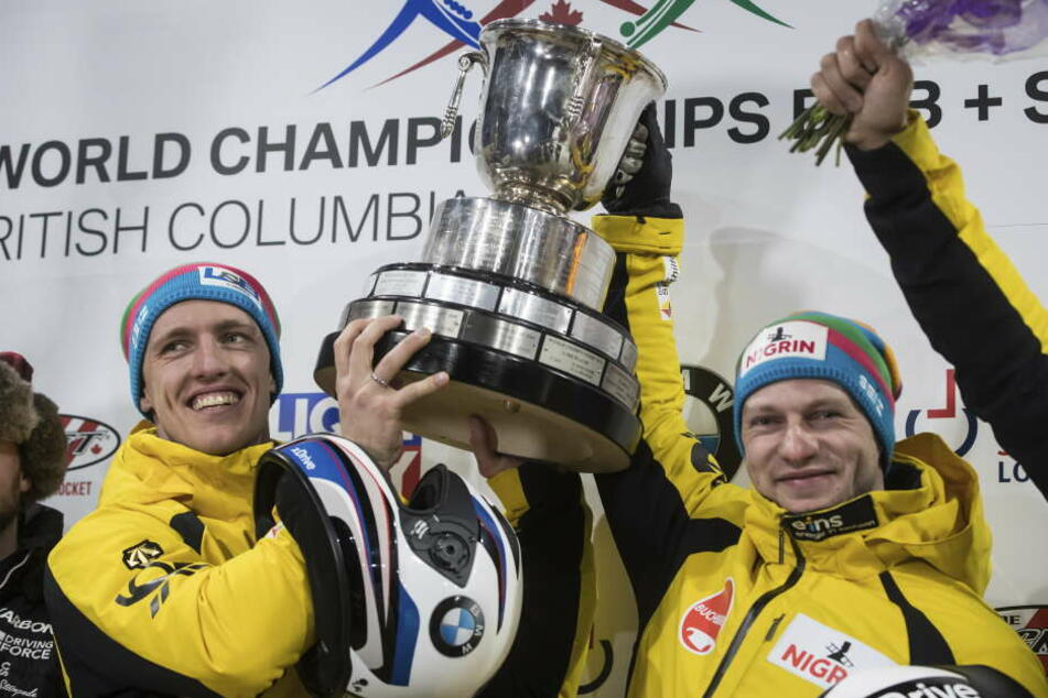 Francesco Friedrich (r) und Thorsten Margis halten den Pokal.