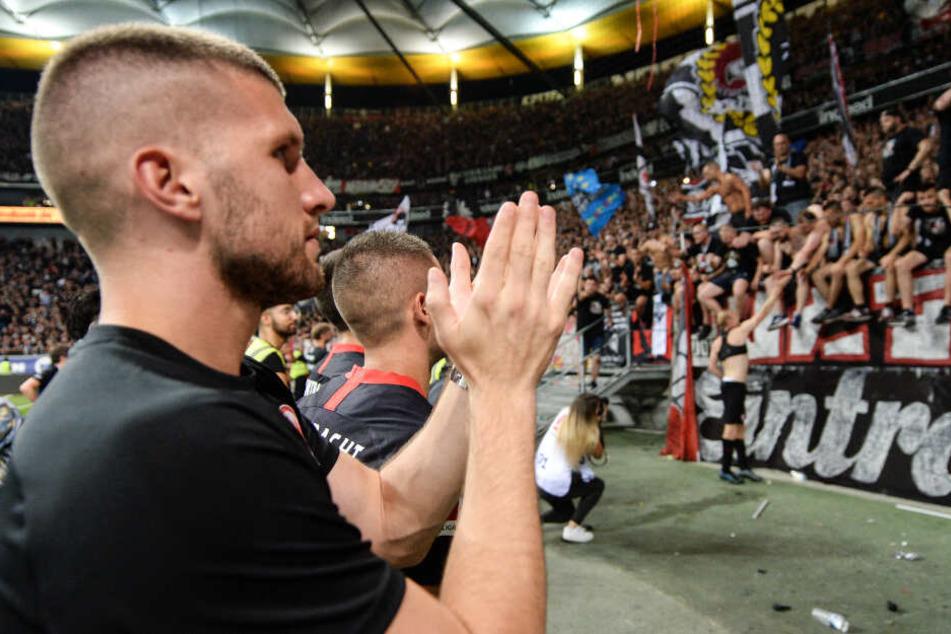 Frankfurts Ante Rebic (l) steht nach dem 3:0-Sieg vor dem Fanblock.