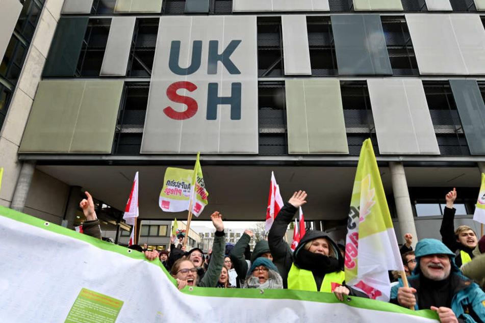 Streikende Pflegekräfte stehen vor dem Universitätsklinikum UKSH.