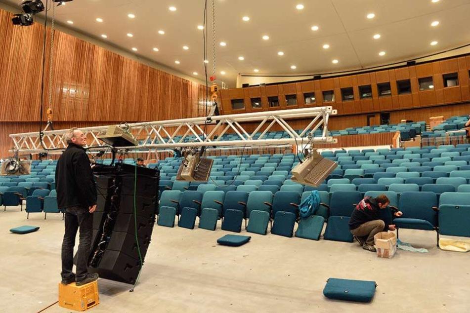 Arbeiter bauen im Auditorium die Sitze wieder ein.