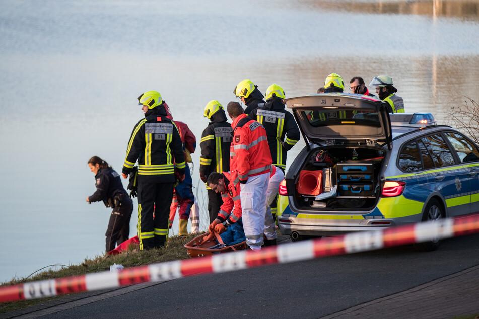 Einsatzkräfte der Polizei und Feuerwehr stehen am Ufer eines Sees. (Symbolbild)