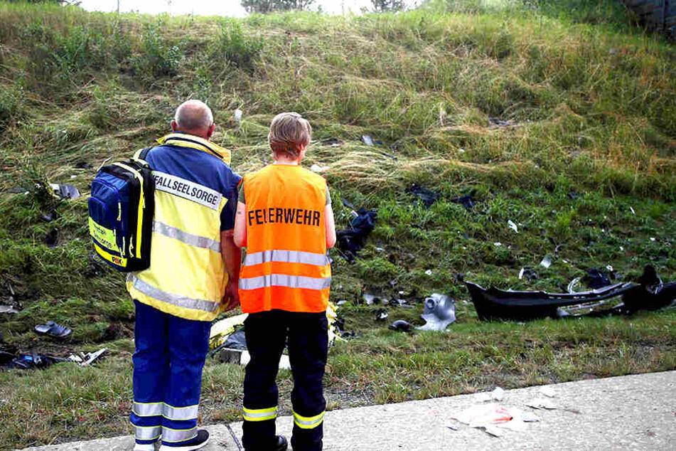 Ein Seelsorger und ein Mitglied der Feuerwehr stehen an der Unfallstelle.