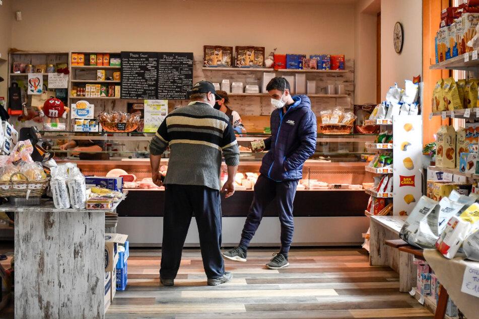 Kunden und die Verkäuferin tragen Mundschutz in einem Lebensmittelgeschäft. Die Ortschaft Ferrera Erbognone liegt in der Corona-Hochburg Lombardei, nur rund 50 Kilometer von Mailand entfernt.