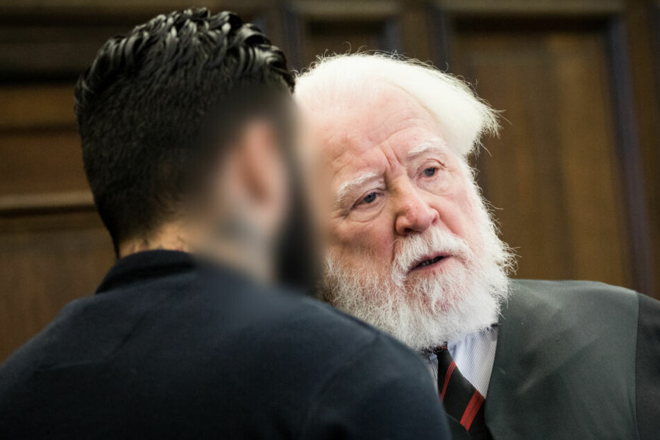 Der Angeklagte und sein Anwalt Wolf Dieter Reinhard unterhalten sich vor Prozessbeginn im Gerichtssaal.